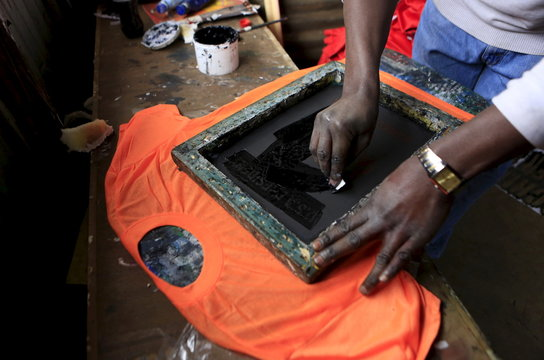 Madegwa applies black paint on a printing screen with an image of U.S. President Obama as he makes t-shirts at his small workshop in Nairobi
