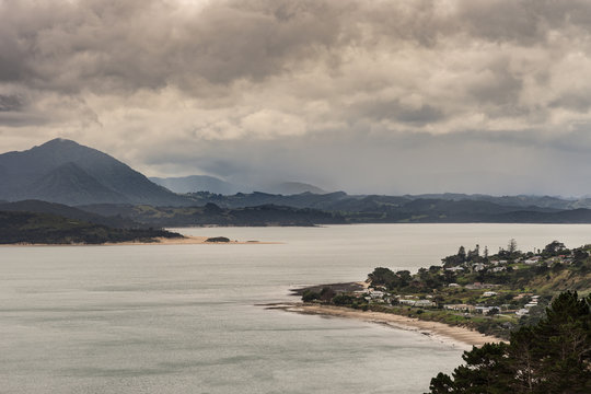Bay of Islands, New Zealand - March 7, 2017: Opononi town and mountains on Hokianga Harbour. All under heavy cloudscape because of approaching cyclone.