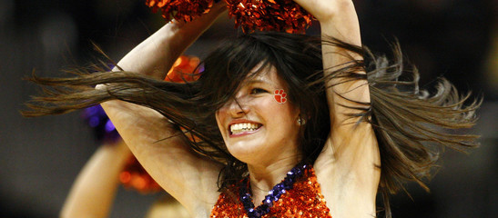 A Clemson Tigers cheerleader performs while playing Virginia Tech Hokies during a college basketball game in Atlanta