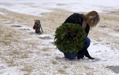 A woman sweeps snow off a grave marker looking for the grave of a military veteran family member to place a Christmas wreath during the Wreaths Across America event at Ft. Logan National Cemetery in Denver
