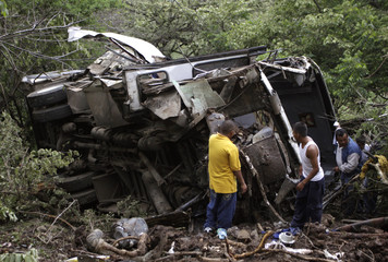 People stand next to the wreckage of a passenger bus after it crashed on a wet road in the southwestern state of Guerrero