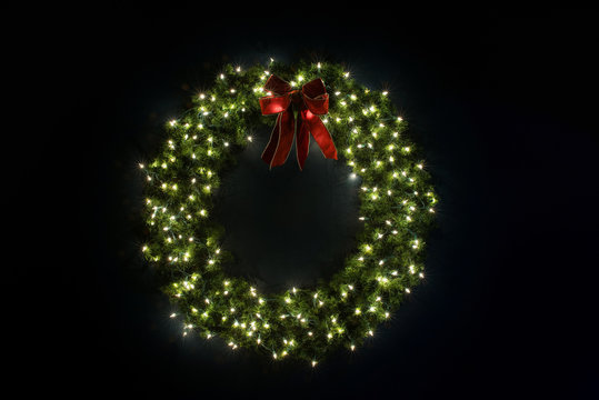 Lit Christmas Wreath On Navy Blue Wall