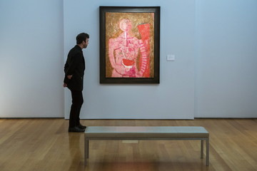 """Man stands near the painting """"Mujer con sandia"""" by artist Rufino Tamayo at a media preview for an upcoming Latin American art sale at Christie's in New York"""