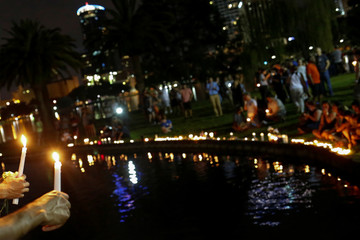 Well wishers hold candles during a vigil to commerate victims of gay night club shooting in Orlando