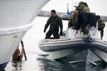 Greek Coast Guard officers in a speedboat approach activists hanging from the anchor's chain of a Turkish-flagged passenger boat carrying migrants to be returned to Turkey, in an attempt to prevent it from leaving the port of Mytilene, on island of Lesbos