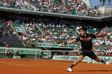 Djokovic of Serbia returns the ball to Hanescu of Romania during the French Open tennis tournament at the Roland Garros stadium in Paris