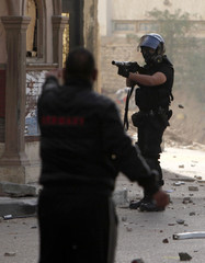 A protester tries to stop a policeman from firing tear gas during clashes in Alexandria