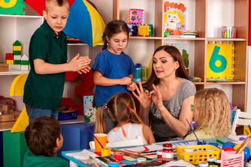 Small students with teacher finger painting in art school class. Break school in painting class. Mom and kids at home. Craft drawing education develops creative abilities of children.