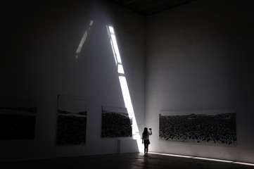 A woman takes a photograph of an exhibition of Chinese landscape paintings at a gallery in Beijing