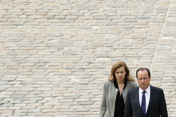 French President Hollande and his companion Trierweiler walk in the courtyard of the Invalides as they follow the procession during a ceremony to pay tribute to late former French Prime Minister Mauroy in Paris