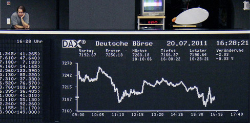 A man watches traders from a balcony near the DAX board at the Frankfurt stock exchange in Frankfurt