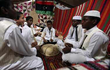 Boys wearing traditional costumes play inside a tent at an event to showcase Libyan culture near the courthouse in Benghazi