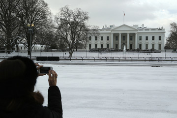 Woman takes pictures of the snow in front of the White House in Washington