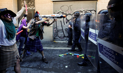 A protester squirts a water gun at Catalan regional police during a protest in Barcelona