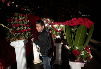 A man sweeps the sidewalk outside a florist decked with roses in preparation for Valentine's Day in Los Angeles