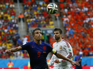 Robin van Persie of the Netherlands eyes the ball as he makes a shot in front of Spain's Pique during their 2014 World Cup Group B soccer match at the Fonte Nova arena in Salvador