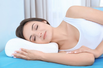 Young woman sleeping on bed with orthopedic pillow at home. Healthy posture concept
