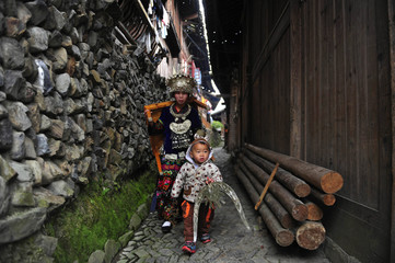 An ethnic Miao woman in traditional clothes carries a table on the first day of the Guzang Festival in Leishan county