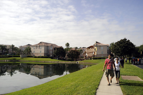 Tourists walk past a section of the Summer Bay Resort after a large sinkhole opened on the property's grounds, in Clermont, Florida