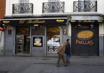 People walk past the Brillante bar with a sign of its specialty, the bocadillo de calamares  (squid sandwich) and a sign showing paella, in Madrid,