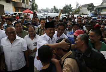 Indonesia's presidential candidate Prabowo Subianto holds a supporter as he walks with Golkar Party chief Aburizal Bakrie during a campaign at Astana Anyar market in Bandung