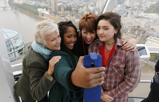 Actress Walters and author Lette pose for a selfie with Dunraven School students Chambers and Symonds during a mentoring session held in the London Eye to mark the third UN International Day of the Girl in central London