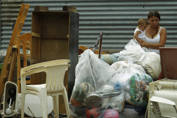 A woman and her son sit among her belongings during an evacuation in the Barrio del Carmen slum near San Jose