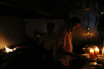 Restaurant workers try to finish up orders in the kitchen during a blackout in Caracas
