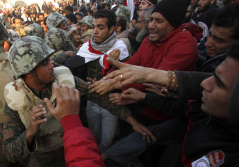 Opposition supporters struggle with members of the Egyptian army in Tahrir Square in Cairo