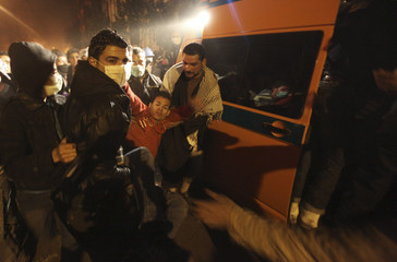 Protesters assist an injured fellow protester into an ambulance after clashes with the army and riot police near Tahrir Square