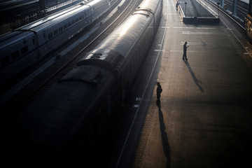 People stand next to a train at a railway station in Nanjing