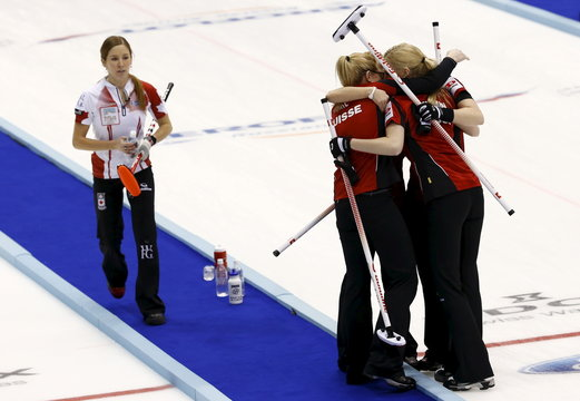 Switzerland players celebrate as Canada's Kaitlyn Lawes leaves the sheet of ice after their game at World Women's Curling Championships