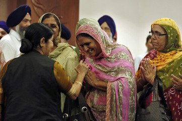 A relative of an Indian worker, who has been kidnapped in Iraq, is being comforted by India's FM Swaraj after their meeting in New Delhi