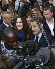 France's President and UMP party candidate for the 2012 French presidential elections Sarkozy exits a voting station with France's first lady Carla Bruni-Sarkozy during the first round of 2012 French presidential election in Paris