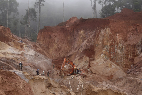 Suriname wildcat miners dig to recover the bodies of seven miners who died when the 20-meter-high dirt wall of a gold mine collapsed, at Money Hill