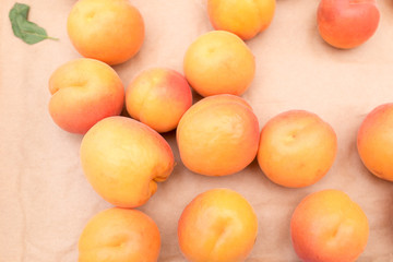 Yellow plums with red blush on light brown paper background. Top view, looking down.
