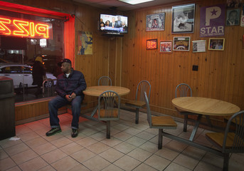 A man glances outside as a live TV broadcast of New York Mayor Bill de Blasio plays above him, in a pizzeria in Harlem, New York