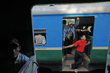 Passengers ride on a train in Yangon
