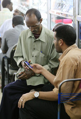 A technician shows a cell phone to a customer in his store in Khartoum