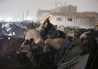 Broken Cement mixer trucks are seen at the site after a landslide hit an industrial park in Shenzhen