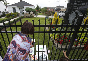 A fan of late musician Michael Jackson takes pictures at his childhood home in Gary, Indiana on his birthday