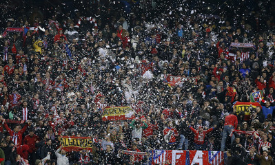 Confetti falls on Atletico Madrid supporters at the start of their Champions League round of 16 second leg soccer match against Bayer Leverkusen in Madrid