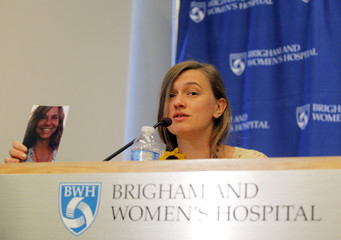 Marinda Righter, daughter of face donor Cheryl Denelli-Righter, holds her mother's photo during a news conference at Brigham and Women's Hospital in Boston