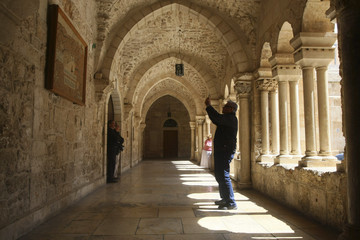 A tourist takes a picture with his mobile phone inside the Church of the Nativity in the West Bank town of Bethlehem