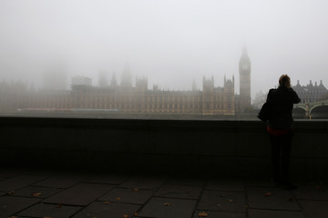 A woman looks at the Big Ben clocktower and the Houses of Parliament during a foggy day in central London