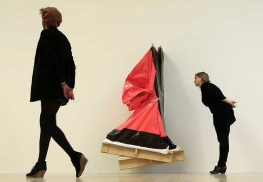 """An employee poses with a work called """"Super Clutter XXL (Pink and Brown)"""" by Angela de la Cruz during the media launch of nominations for the Turner Prize 2010, at the Tate Britain gallery in London"""