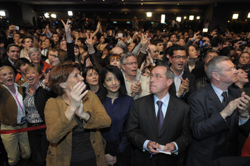 Interior Minister Claude Gueant reacts with ministers to early results for incumbent Nicolas Sarkozy at the Mutualite meeting hall in Paris