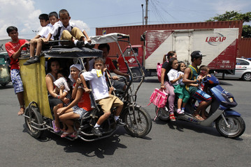 School children ride a tricycle cab on their way to school in Manila