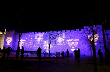 People walk past an image of a Menorah, the Hebrew name for the candle-holder used during the Jewish holiday of Hanukkah, is projected on a wall surrounding Jerusalem's Old City