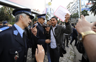 Protester argues with police officers as he protests against U.S.-backed plans to broaden mandate of UN peacekeepers in the disputed Western Sahara, in Casablanca